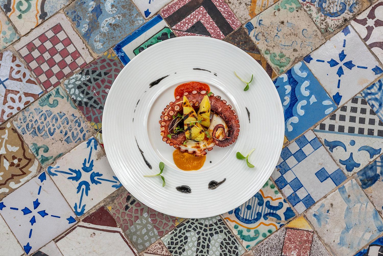 Polpo alla griglia con vellutata di peperoni e salsa al nero di seppia